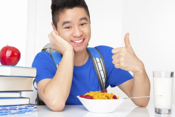 Smiling male student eating breakfast