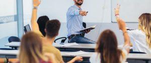 Un homme habillé d'une chemise bleue claire et d'un jean bleu marine est assis sur une tableau et pointe du bout du doigt les élèves en face de lui. Les élèves lèvent le bras. Un des élèves porte un t-shirt jaune, deux autres en portent un blanc.