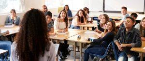 Des élèves dont des filles et un garçon sont assis autour de tables